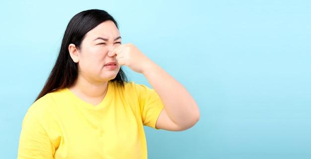 Retrato asia mujer se siente mal, sobre fondo azul en studio
