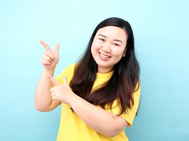 Retrato asia mujeres con un dedo, sobre un fondo azul en estudio.