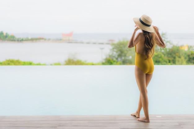 Retrato asiática hermosa joven feliz sonrisa relajarse en la piscina al aire libre en vacaciones