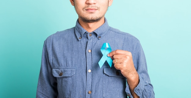 Retrato asiático feliz guapo posando él sosteniendo cinta azul claro