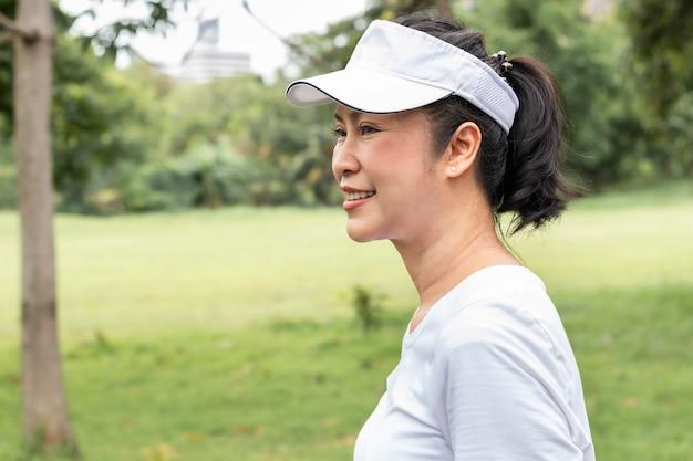 Retrato asiático hermoso de la mujer mayor que piensa y que se relaja en el parque.