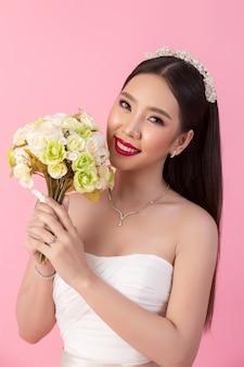 Retrato asiático hermoso de la novia en estudio rosado