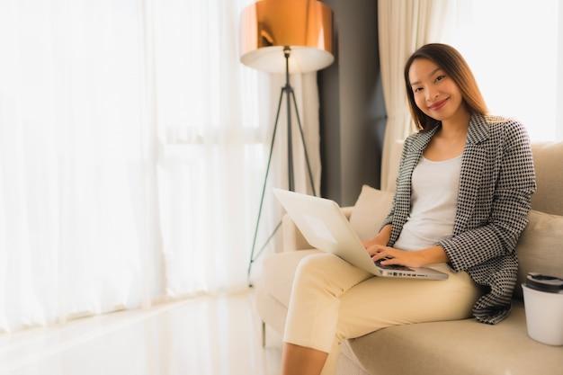 Retrato asiático joven hermoso que usa la computadora y la computadora portátil con la taza de café que se sienta en el sofá