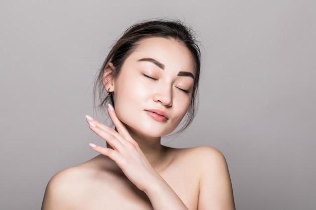 Retrato asiático del primer de la cara de la belleza de la mujer. hermosa y atractiva modelo asiático femenino de raza mixta con piel perfecta aislada en la pared gris