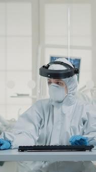 Retrato de asistente dental escribiendo en el teclado de la computadora con uniforme de protección con protector facial, máscara, guantes y mono. enfermera de estomatología con tecnología de monitor en la clínica bucal