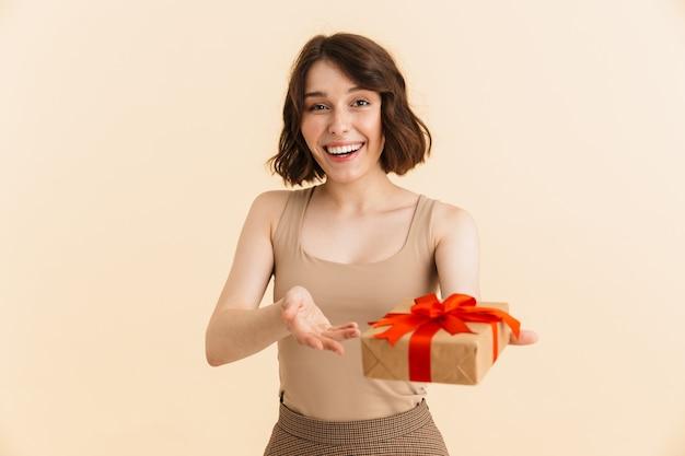 Retrato de asombrada mujer caucásica de 20 años vestida con ropa casual sonriendo mientras sostiene la caja presente aislada