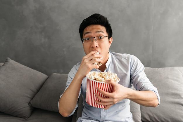Retrato de un asustado joven asiático comiendo palomitas de maíz