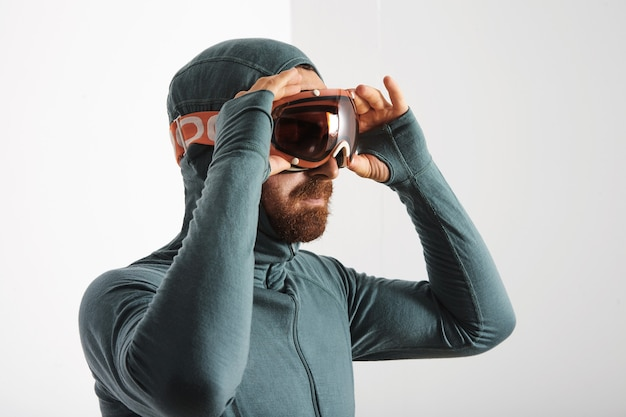 Retrato de atleta masculino barbudo en suite térmica de capa base lleva gafas de snowboard