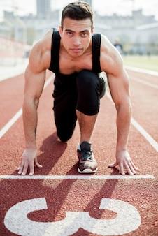 Retrato de un atleta masculino confiado en la línea de salida de la pista de carreras