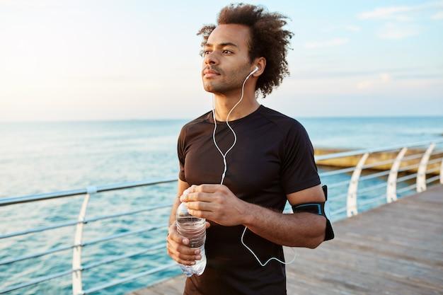 Retrato de un atleta masculino de piel oscura concentrada y mediadora con cabello tupido sosteniendo una botella de agua mineral en sus manos.