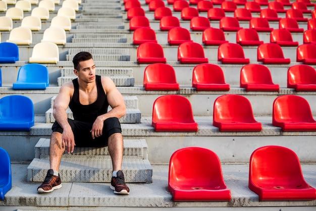 Retrato de un atleta masculino sentado en los escalones de la grada de hormigón