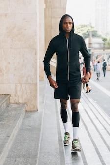 Retrato de un atleta masculino en sudadera con capucha negra caminando cerca de la escalera
