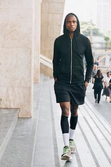 Retrato de un atleta masculino en sudadera con capucha negra que camina cerca de la escalera en el aire libre