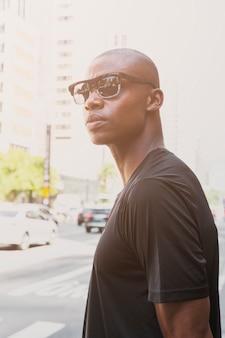 Retrato de un atleta de sexo masculino joven que se coloca en las gafas de sol que llevan del camino que miran lejos