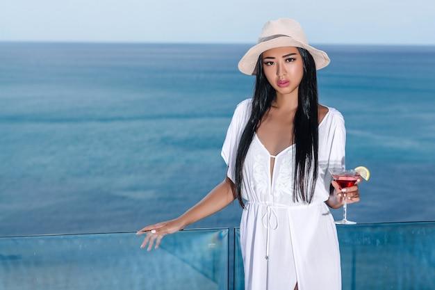 El retrato de la atractiva chica asiática con un sombrero que sostiene una copa de cóctel en sus manos es cosmopolita. hermosa vista al mar sobre fondo borroso