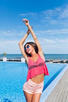 Retrato de una atractiva chica morena con el pelo largo posando para la cámara junto a la piscina. ella está sonriendo y sosteniendo las manos arriba.