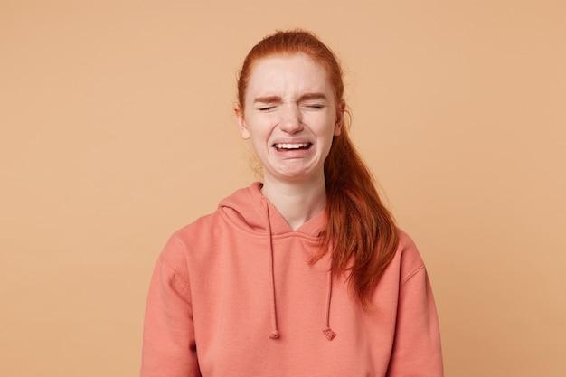 Retrato de una atractiva chica pelirroja que está llorando sufre de amor no correspondido