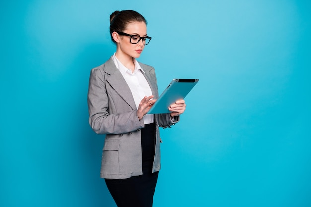 Retrato de una atractiva dama calificada especializada agente broker investigando datos cv utilizando un dispositivo aislado sobre fondo de color azul brillante
