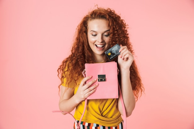 Retrato de una atractiva joven alegre con el pelo rojo largo y rizado que se encuentran aisladas, poniendo la tarjeta de crédito en su bolso