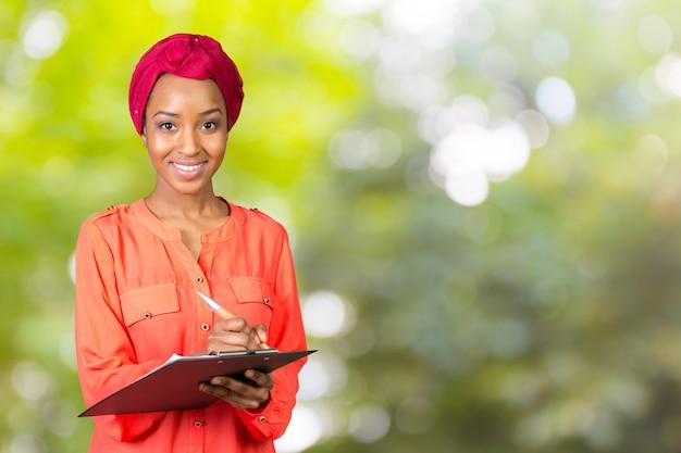 Retrato de una atractiva joven empresaria africana americana con portapapeles