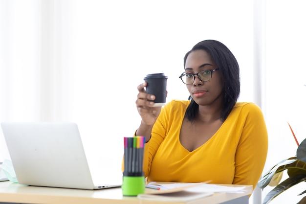 Retrato atractiva joven empresaria afroamericana bebiendo café negro en la oficina en casa moderna.