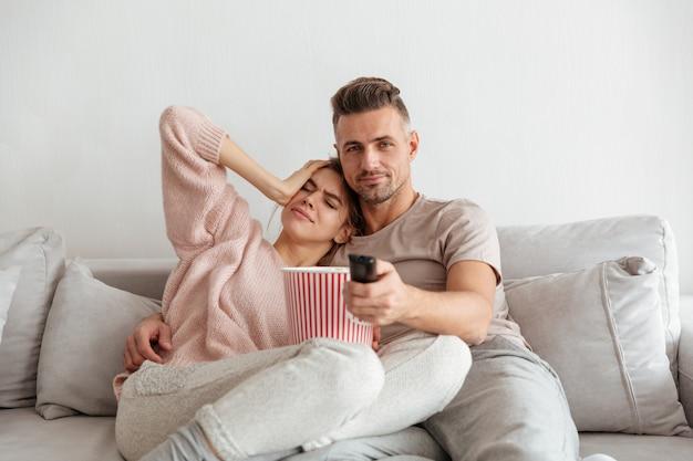 Retrato de una atractiva joven pareja comiendo palomitas de maíz