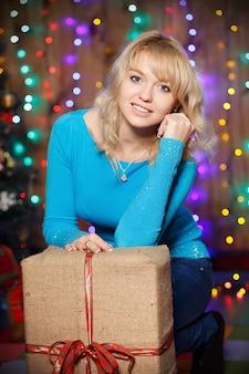 Retrato de atractiva joven rubia encantadora con un gran regalo en el interior de la caja con adornos navideños