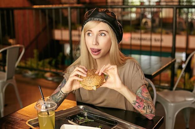 Retrato de atractiva joven rubia tatuada en camiseta beige y boina negra comiendo hamburguesa y lamiendo sus labios, posando sobre el interior de la cafetería moderna