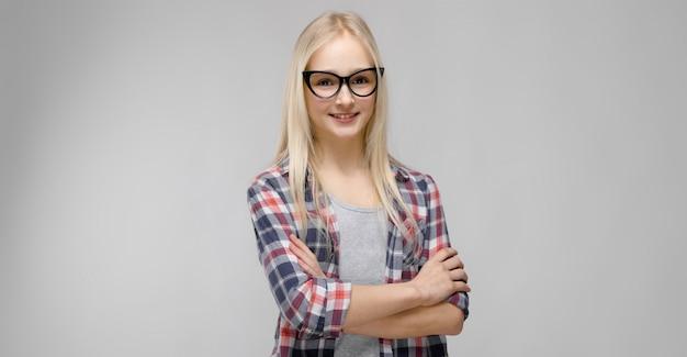 Retrato de la atractiva muchacha adolescente rubia adorable en ropa a cuadros en vasos con los brazos cruzados sobre fondo gris