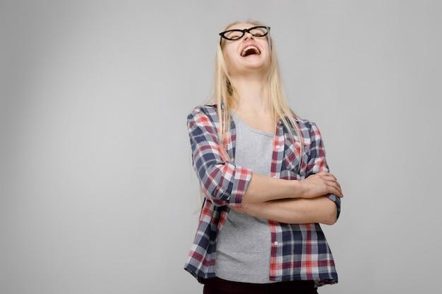 Retrato de la atractiva muchacha adolescente rubia adorable en ropa a cuadros en vasos con los brazos cruzados sobre gris