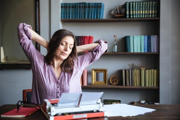 Retrato de una atractiva mujer autora descansando y estirando las manos