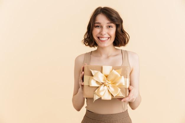 Retrato de atractiva mujer caucásica de 20 años vestida con ropa casual sonriendo mientras sostiene la caja presente aislada