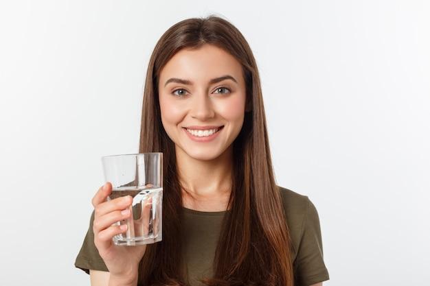 Retrato de atractiva mujer caucásica sonriente agua potable.