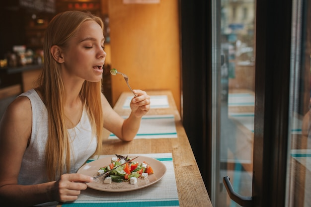 Retrato de atractiva mujer caucásica sonriente comiendo ensalada