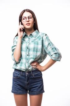 Retrato de atractiva mujer hispana en camiseta azul hablando en su celular mientras está de pie y sonriendo en el estudio