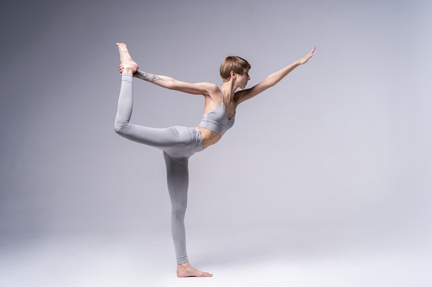Retrato de atractiva mujer joven feliz trabajando en el interior, haciendo ejercicio de yoga