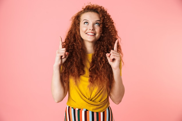 Retrato de una atractiva mujer joven sonriente con pelo rojo largo y rizado que se encuentran aisladas, presentando espacio de copia