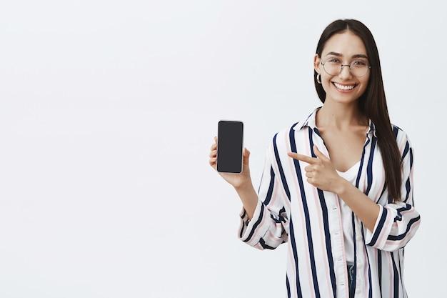 Retrato de atractiva mujer de moda complacida con gafas y blusa, mostrando la pantalla en el teléfono y apuntando al dispositivo con el dedo índice, sonriendo ampliamente