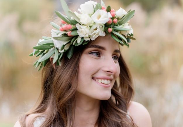 Retrato de una atractiva mujer morena en una corona hecha de eustomas con una hermosa sonrisa