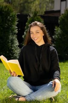 Retrato de atractiva mujer morena de pelo largo sonriente vestida con sudadera con capucha negra sentada sobre césped verde leyendo libro amarillo