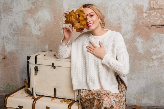 Retrato de atractiva mujer rubia elegante sonriente en suéter de punto blanco sentado en maletas en la calle contra la pared vintage