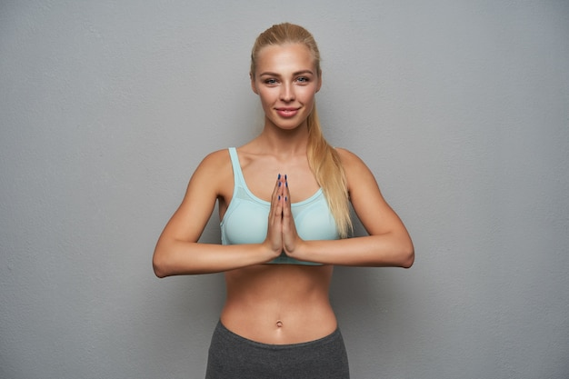 Retrato de atractiva mujer rubia de pelo largo deportivo haciendo yoga sobre fondo gris claro, manteniendo las palmas dobladas y mirando positivamente a la cámara con una sonrisa suave