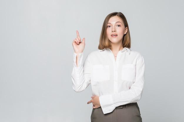 Retrato de atractiva mujer sonriente apuntando hacia arriba aislado en la pared blanca