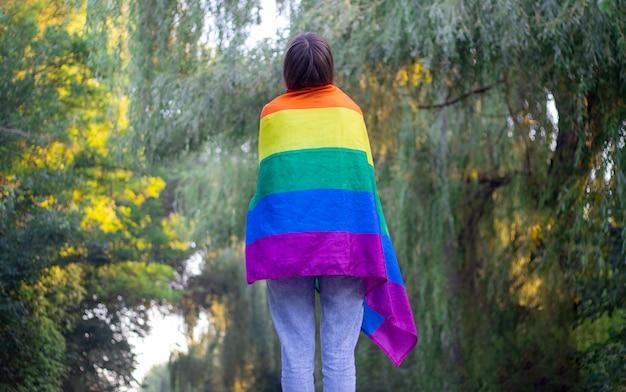 Retrato de una atractiva mujer sosteniendo una bandera gay lgbt arco iris sobre sus hombros, mirando hacia un lado.
