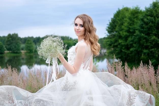 Retrato de atractiva novia elegante joven sonriente en vestido de novia blanco con ramo de novia en la mano, maquillaje y peinado