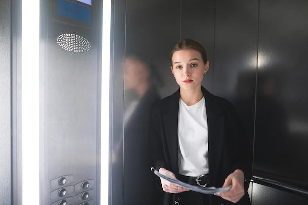 Retrato de una atractiva oficinista pacífica sosteniendo los documentos en el ascensor.