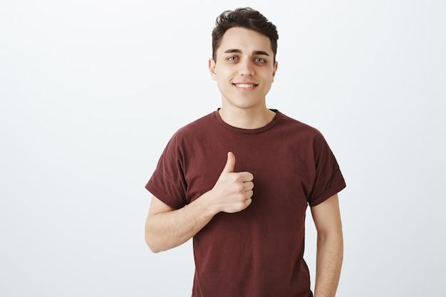 Retrato de atractivo empresario masculino seguro en traje casual con pulgar hacia arriba