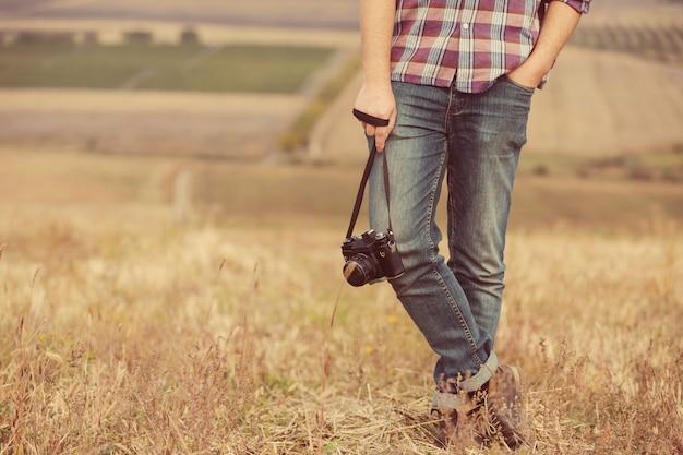 Retrato de atractivo fotógrafo masculino al aire libre al atardecer. joven con una cámara en mano