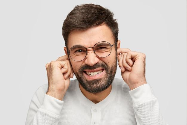 Retrato de atractivo hombre sin afeitar tapona los oídos mientras escucha un sonido molesto, frunce el ceño, aprieta los dientes