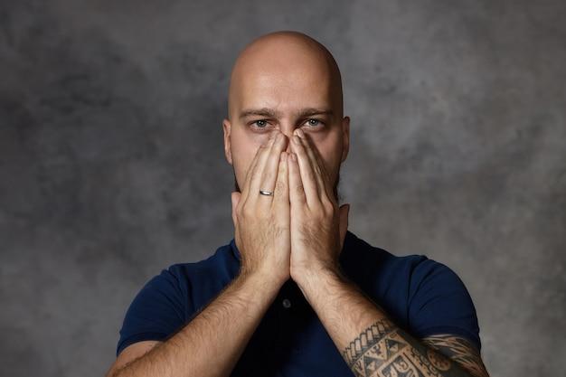 Retrato de atractivo hombre calvo con tatuaje que cubre la boca y la nariz con ambas manos, aguantando la respiración debido al mal olor. hombre cansado agotado frustrado posando en stduio, manteniendo las manos en la cara